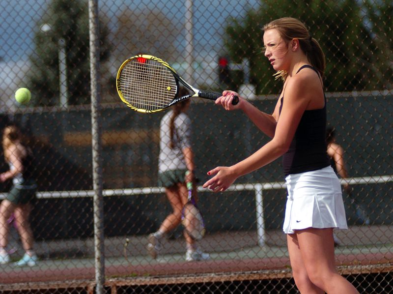 by: DAN BROOD - BIG WIN -- Tualatin High School sophomore Riley Steele hits a shot during No. 1 doubles play during Friday's match at Tigard. Steele and Debbie Kim scored a 7-6 (7-5), 6-4 victory.