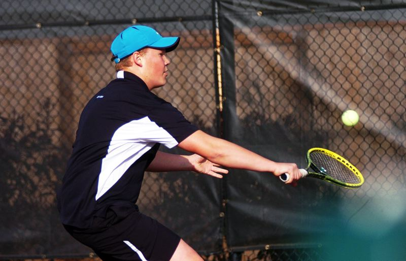 by: DAN BROOD - BACK AT IT -- Sherwood's Anders Joergensen hits a backhand shot during his win over Canby's Austin Evans.