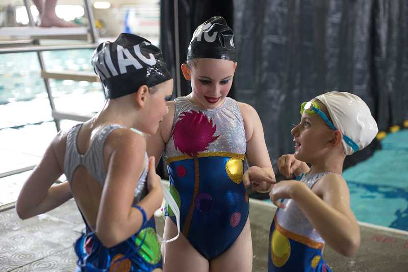 by: TIMES PHOTO: JONATHAN HOUSE - Multnomah Athletic Club synchro swimmers chat excitedly after their routine.