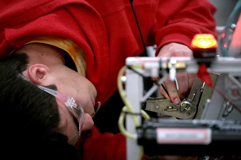 by: TIMES PHOTO: JONATHAN HOUSE - Catlin Gabel's Evan Champman makes some repairs and adjustments in between matches at the Pacific Northwest FIRST Robotics District Championship on Friday.