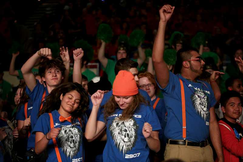 by: TIMES PHOTO: JONATHAN HOUSE - Members of the winning Lion Robotics Team from Auburn, Wash., dance at the conclusion of the Pacific Northwest FIRST Robotics District Championship.