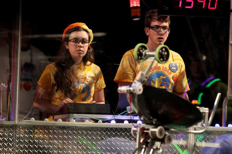 by: TIMES PHOTO: JONATHAN HOUSE - Iman Wahle and Rushdi Abualhaija drive the Catlin Gabel 'Flaming Chickens' robot during the Pacific Northwest FIRST Robotics District Championship.