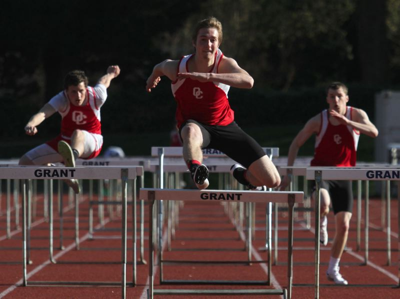 by: JON HOUSE - Oregon City junior Austin DeWitz (center) heads for a win in the high hurdles in last weeks Three Rivers League dual meet at Grant.