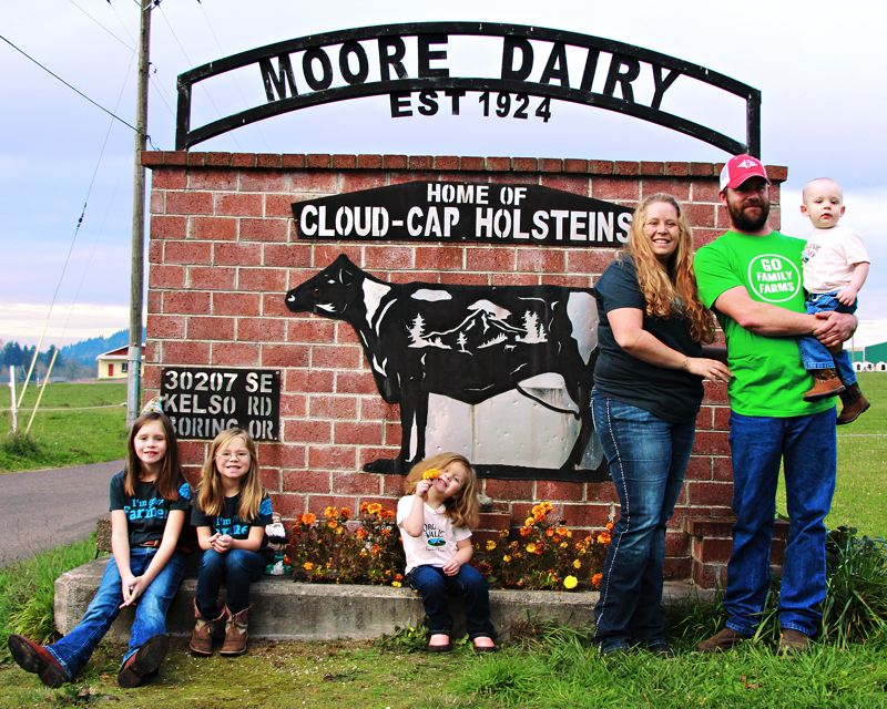 by: CONTRIBUTED PHOTO: MELISSA COLLMAN - Melissa and Andy Collman in front of the sign for their award-winning farm with children William, in his dads arms, and from left, daughters Elizabeth, Autumn and Hailey.