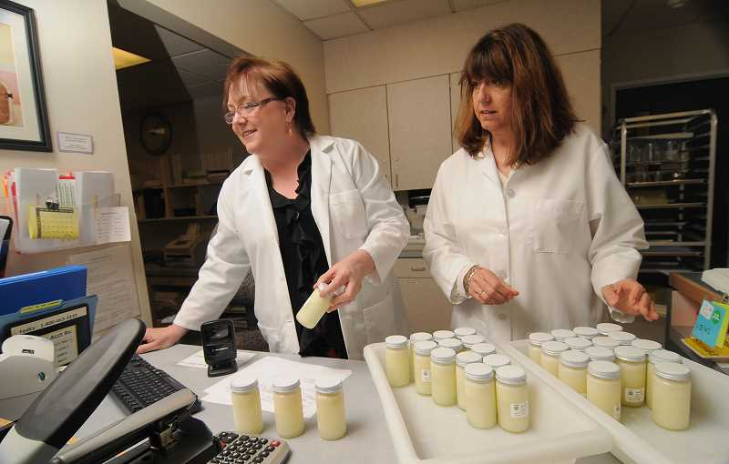 by: REVIEW/TIDINGS PHOTOS: VERN UYETAKE - Lesley Mondeaux, left, and Joanne Ransom, both of Lake Oswego, are the co-directors of Northwest Mothers Milk Bank. Here they are packing orders of donated human milk for delivery to area hospitals.