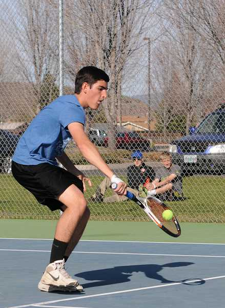 by: LON AUSTIN/CENTRAL OREGONIAN - Pedro de Souza comes to the net to volley the ball as he defeats Bend's Sean Hebert 6-2, 6-2 in the No. 1 singles match of the Cowboys' dual over Bend.