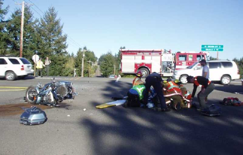 by: OREGON STATE POLICE - Police and paramedics treat an injured Molalla motorcyclist injured in a crash off Highway 213 Sunday afternoon.