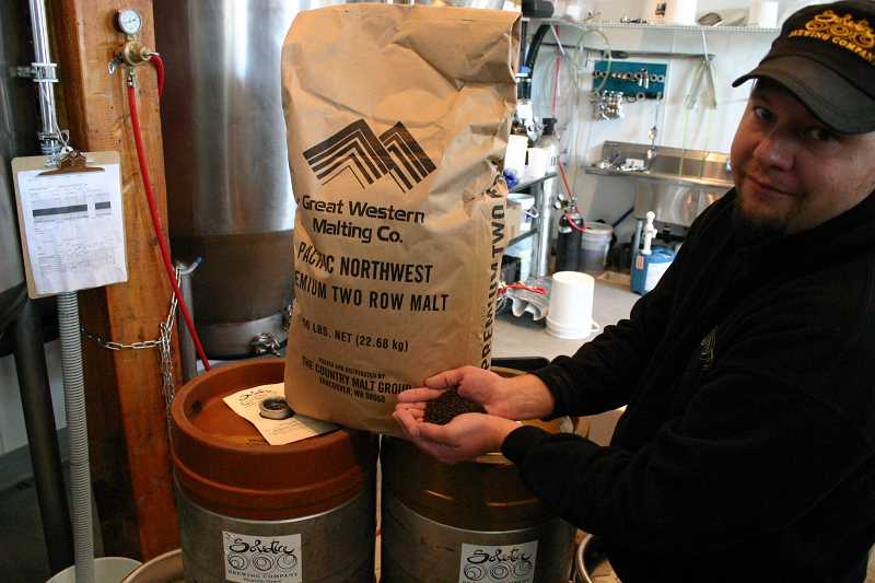 by: JASON CHANEY - Solstice Brewing Company co-owner Joe Barker displays some of the grains he uses to brew beer.