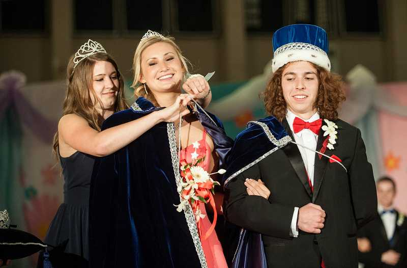 by: SPOKESMAN PHOTO: JOSH KULLA - Last year's Springfest Queen, Madi Bean, fits 2014 Queen Madison Rasmussen with her cape while King Andrew Farrington looks on.