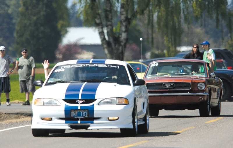 by: PHIL HAWKINS - Mustang drivers parade through the streets of West Woodburn, waving to passers-by near the Woodburn Dragstrip, which hosted the world record-breaking event Saturday.