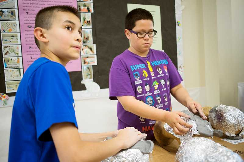 Jose Garfias and Jose Lopez, both students in Free Orchards art literacy program, enjoy a mask-making session.