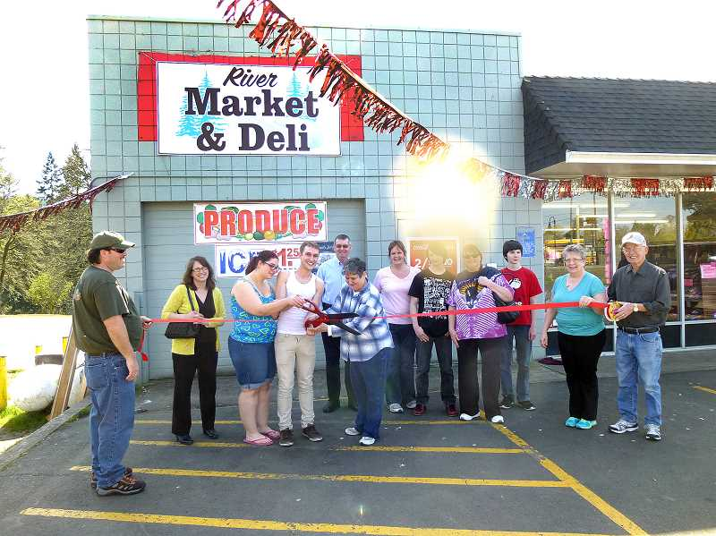 by: CONTRIBUTED - City leaders and community members gather around River Market & Deli owner Zack Simpson for a Ribbon Cutting Ceremony on Monday, April 7.