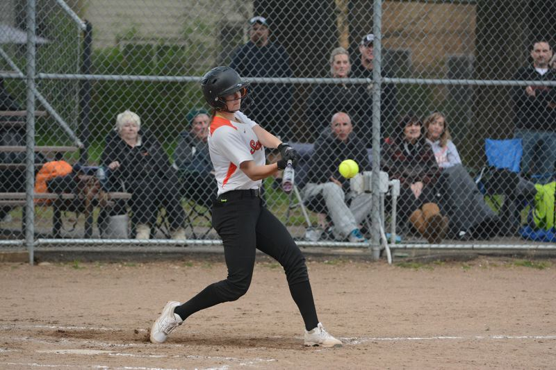 by: JOHN WILLIAM HOWARD - Senior Lacey Updike swings for a double, scoring two runners in the bottom of the third to put Scappoose on top 10-1 over Tillamook.