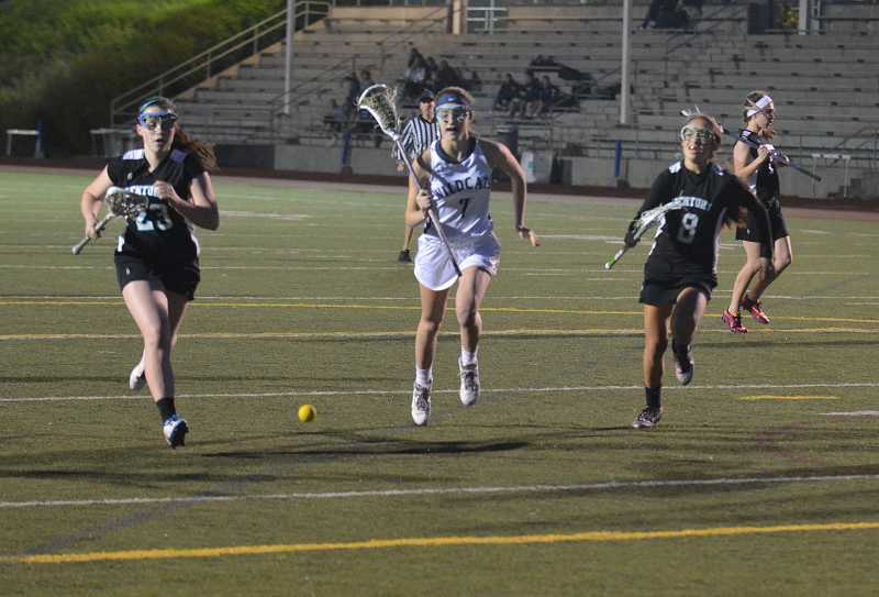 by: JEFF GOODMAN / PAMPLIN MEDIA GROUP - McKena Eisenbrandt (center) and the Wilsonville girls lacrosse team crushed Century 19-3 in a league game April 8 at Randall Stadium.