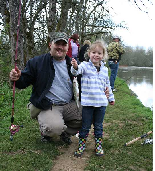 by: JIM BESEDA - Avery Wurdinger, 4, right, holds up the first fish she has ever caught alongside her dad, Sam Wurdinger, during Saturday's ODFW-sponsored event at Shorty's Pond.