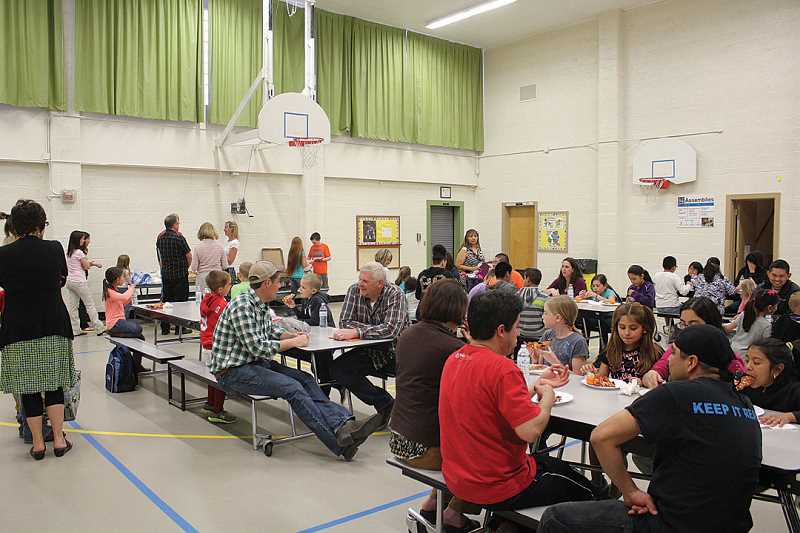 by: SUSAN MATHENY - Metolius Elementary students enjoy a pizza dinner with their families Monday night following a presentation to the 509-J School Board.