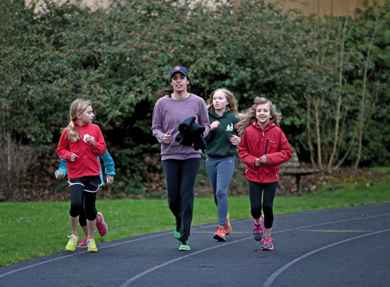 by: TRIBUNE PHOTO: JONATHAN HOUSE - Coach Flavia Deandrade leads some of the group of Girls on the Run at the Duniway Park track. The nonprofit group helps young girls learn to avoid stereotypes and find positive images for their lives.