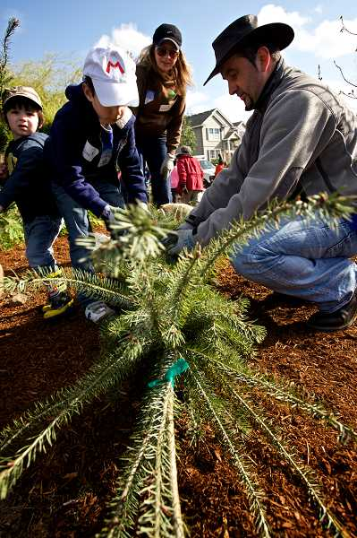 by: TIMES PHOTO: JAIME VALDEZ - Mika Tomic, right, his sons, Stefan, 2, and Luka, 7, and his wife, Svjetlana, participate in the Arbor Day event at the corner of Southwest Barrows Road and 157th Avenue.