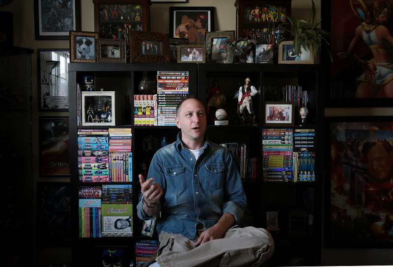by: TIMES PHOTO: JONATHAN HOUSE - Bluewater Productions President Darren Davis talks about his time in the comic book industry in front of his large wall of memorabilia.