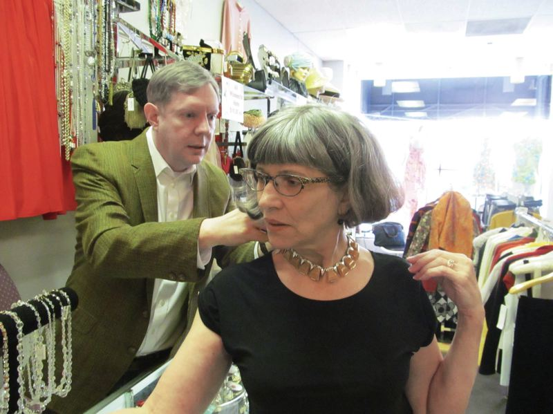 by: COURTESY OF DICK TRTEK - John Cosgrove, owner of Decades in downtown Portland, helps customer Ellen Bartholomew try on a vintage Bakelite necklace. The popular vintage clothing store will be closing April 26.