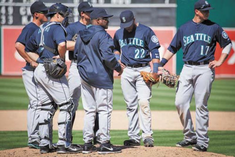 by: COURTESY OF MEG WILLIAMS - Seattle Mariners manager Lloyd McClendon confers with players on the mound. McClendon attributes some of Seattles early-season success to regular 20-minute fielding sessions three hours before each game.
