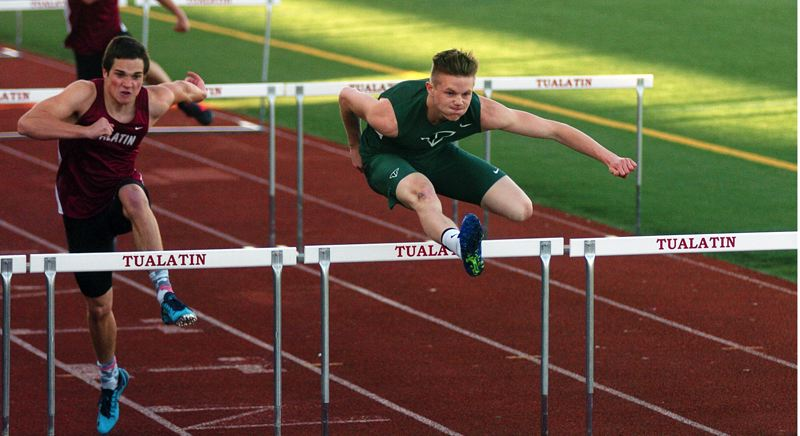 by: DAN BROOD - IN THE LEAD -- Tigard senior Michael Roberts (right) is in first place going over the final obstacle in the 110-meter high hurdles.