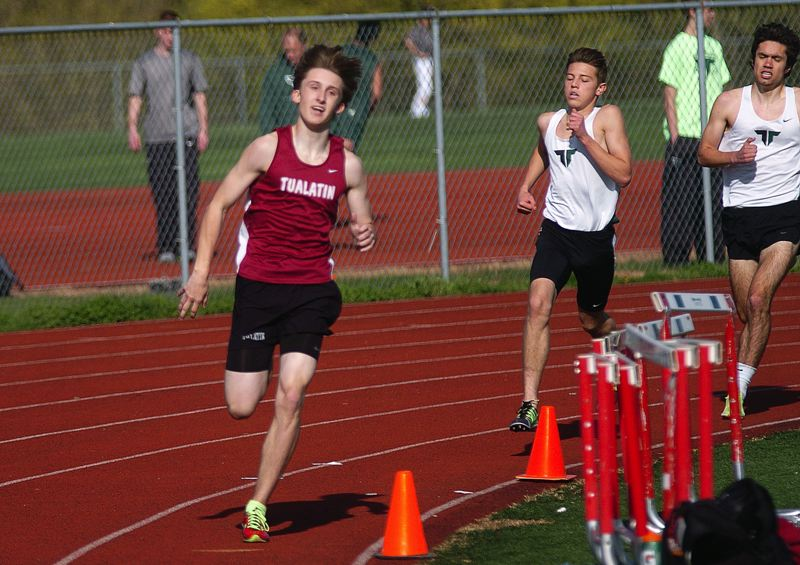 by: DAN BROOD - KICKING -- Tualatin junior Matthew Lovos (left) has the lead as he enters the final stretch of the 1,500.