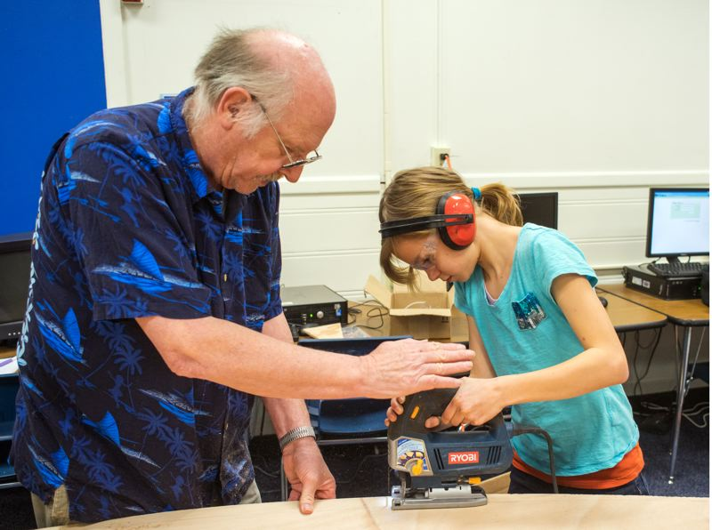 by: HILLSBORO TRIBUNE PHOTOS: CHASE ALLGOOD - Volunteer Tom Nelson helps Farmington View fifth-grader Julia Mas cut the bottom of the boat the students are building.