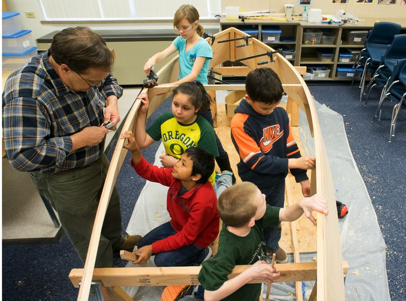by: HILLSBORO TRIBUNE PHOTO: CHASE ALLGOOD - Peter Crim, left, of Wind & Oar Boat School, mentors fifth-graders in building an 11-foot wooden skiff.