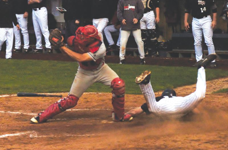 by: ESTACADA NEWS: PARKER LEE - Clackamas CC catcher Joe Strand waits for the throw, while Mt. Hoods John Welborn slides across home plate.