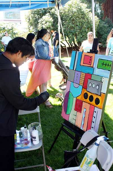 by: NEWS-TIMES PHOTO: DOUG BURKHARDT - Forest Grove's Plata Garza painted an abstract under the artists' tent Sunday at the Latino Cultural Festival in Hillsboro.