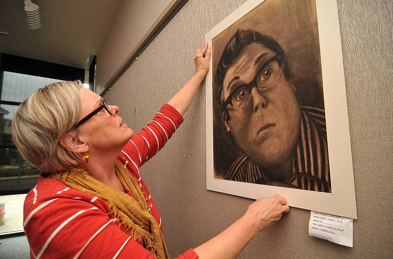 by: TIDINGS PHOTO: VERN UYETAKE - Diane Gauthier hangs the charcoal drawing of an 'Important Person' by WLHS senior Josh Jaeger.
