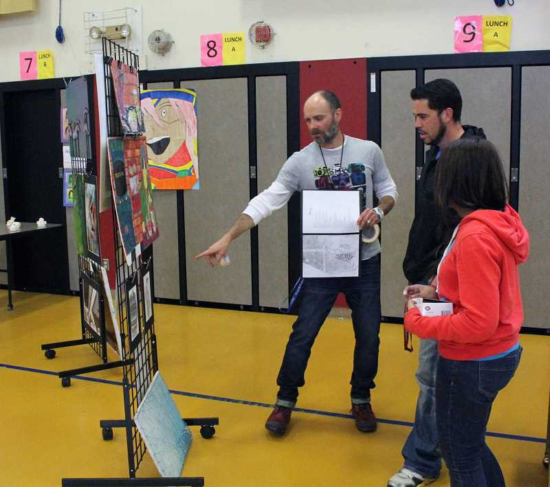 by: TYLER FRANCKE - Michael Dodson, left, discusses some of the high schoolers' work with attendees.
