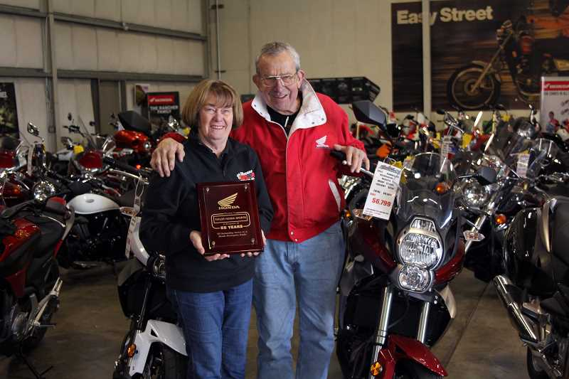 by: TYLER FRANCKE - John and Josele Taylor, owners of Taylor Motorcycles Inc., pose in their showroom last week. Over the weekend, the couple celebrated their 50th year in business at their headquarters on Highway 99E in Woodburn.