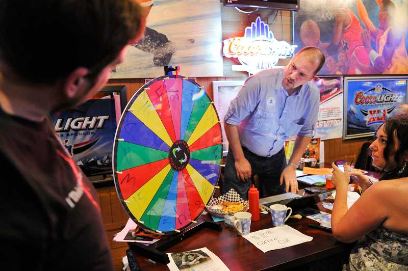 by: TIMES PHOTOS: JOHN LARIVIERE - Doug Pleasants (left) watches the spinning wheel with Team Dominic event organizer Chris Johnsen to find out what song he will sing during a karaoke challenge at the Sports Page.