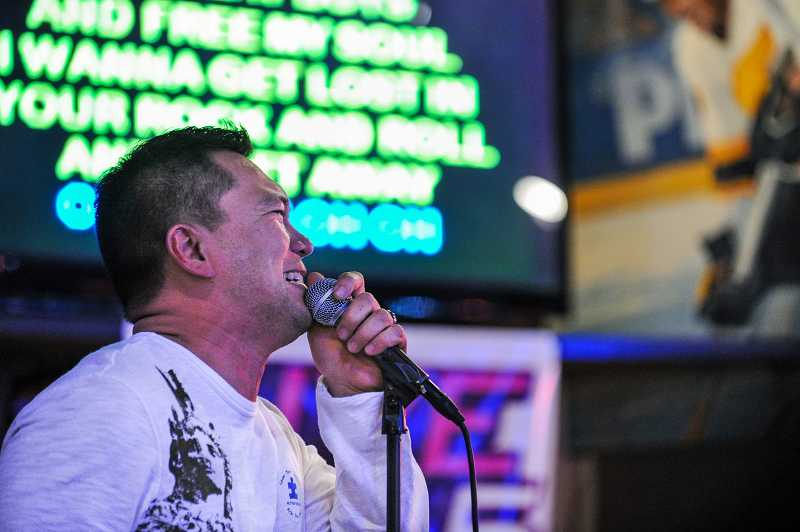 by: TIMES PHOTOS: JOHN LARIVIERE - Rick Sohler of Beaverton sings 'Drift Away' as part of the Team Dominic fundraiser for Autism Speaks at the Sports Page in Beaverton.
