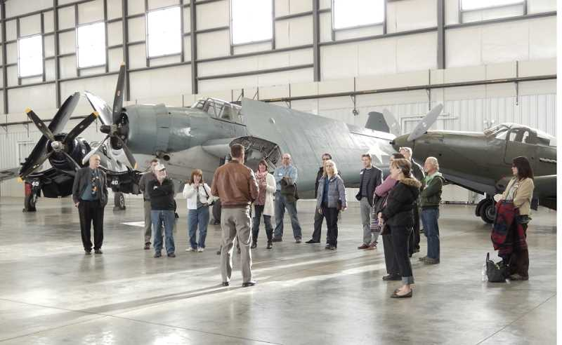 by: TOM BROWN - Several of Jack Erickson's collection of World War II aircraft are lined up behind participants in Jefferson County's Economic Development for Central Oregon tour on April 16. Kevin McCullough, co-owner of Erickson Aero Tanker, talks about the business to the group, which toured the Aero Tanker hangar.