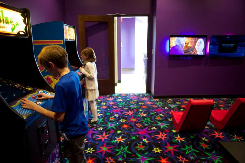 by: TIMES PHOTO: JAIME VALDEZ - Ian Brennan, 10, and Megan Macaulay, 8, pass time by  playing video games in the game room at Seirk Orthodontics before getting their braces checked on.