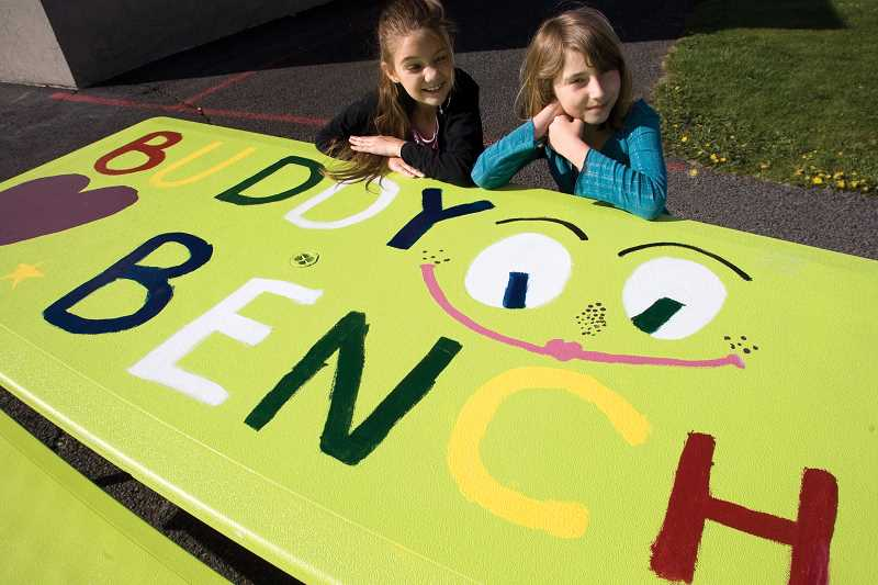 by: KEVIN SPERL - Ivy Cater and Jade Henry sit at the buddy bench they designed for the school playground.
