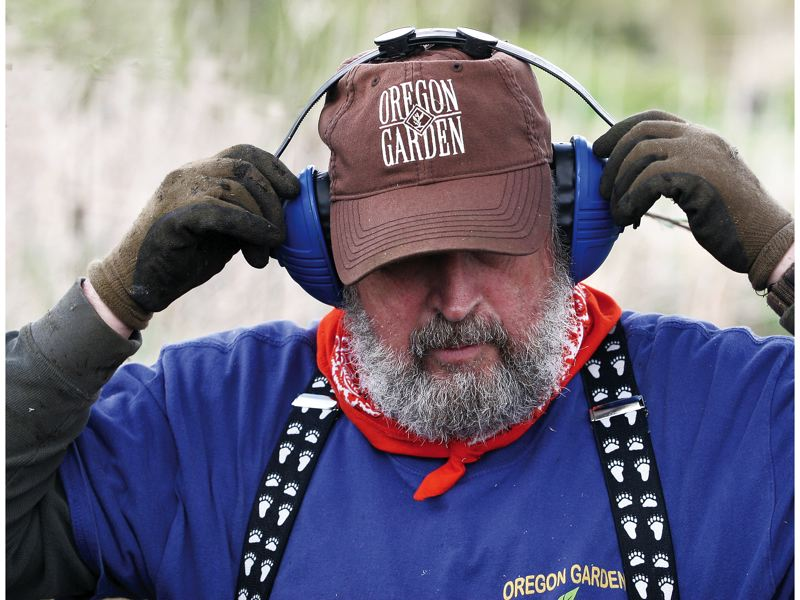 by:  JIM CLARK / PAMPLIN MEDIA GROUP - Oregon Garden volunteer Ed Green says hes not a gardener, but if theres a chore to do there, he's the man.