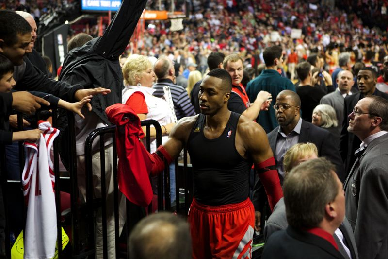 by: TRIBUNE PHOTO: JAIME VALDEZ - Houston Rockets center Dwight Howard hands his jersey to a fan as he leaves the court after Sunday's 123-120 overtime loss to the Trail Blazers at Moda Center.