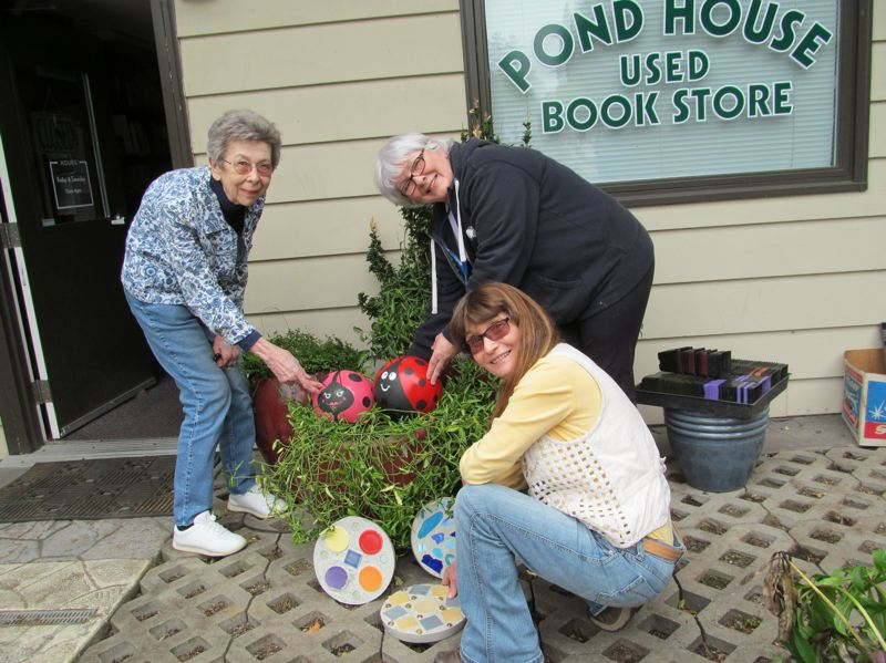 by: PHOTO BY ELLEN SPITALERI - Audrey Trubshaw and Pat Hodgin show off the ladybugs, while  Heidi Peterson sets up the stepping stones to be sold at the plant sale on May 10.