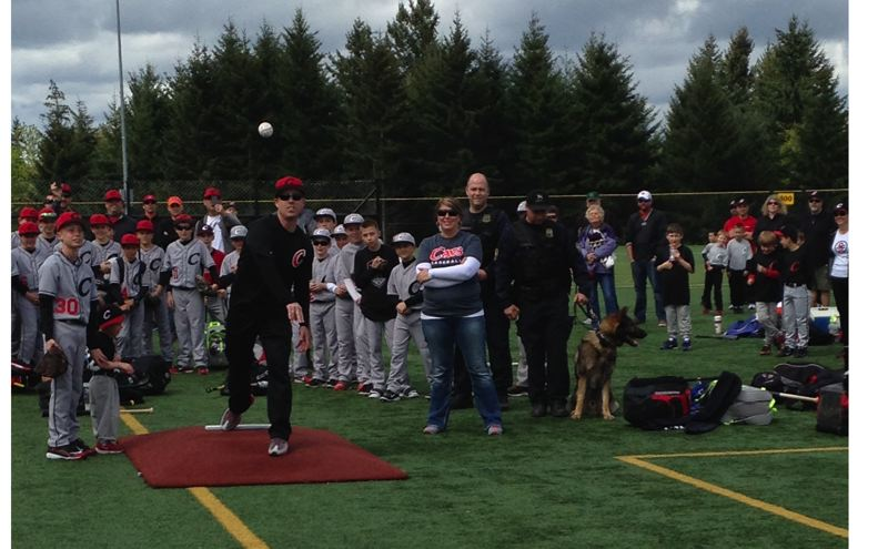 by: PHOTO BY: CINDY FREE-FETTY - Portland Police Officer Jeff Dorn throws the first pitch Saturday at the opening ceremonies for Clackamas Junior Baseball.