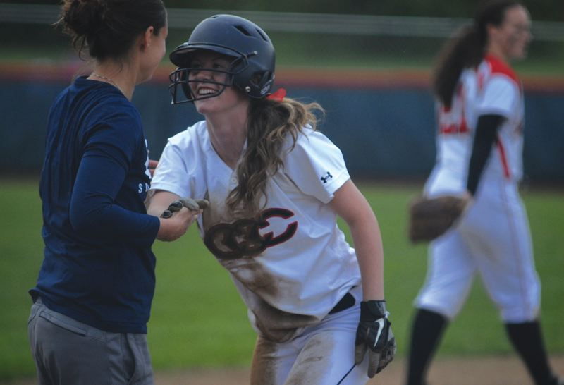 by: ESTACADA NEWS: DAVID BALL - Clackamas Cassidy Edwards is greeted at third base by head coach Jessica Buel during the teams five-run spurt in the fourth inning of Game 2 Monday.