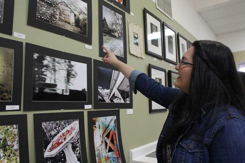 by: LINDSAY KEEFER - Montse Astorga points to her favorite photograph at the IB Art Show exhibit Thursday.