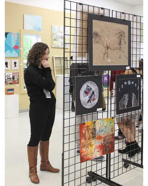 by: LINDSAY KEEFER - WACA teacher Mindy Brooks-Gershuny examines her students' paintings.