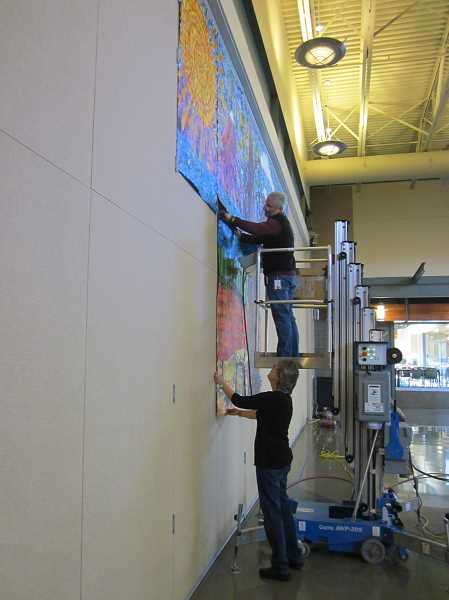 by: SHERWOOD GAZETTE: BARBARA SHERMAN - As Sherwood School District employee Ian McNeely attaches one of 14 panels to a wall at Edy Ridge Elementary that form a gigantic mural, Maggie Englund, the artist in residence who worked with students to design and create it, holds it in place at the bottom.