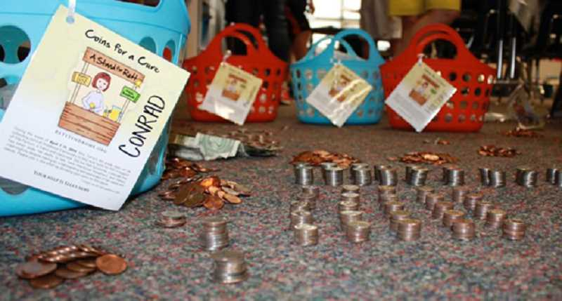by: COURTESY OF BETH FARNUM - Coins for a Cure posters were sent home with Middleton students and also posted all over the school along with a stack of uncounted coins and some collection bags.