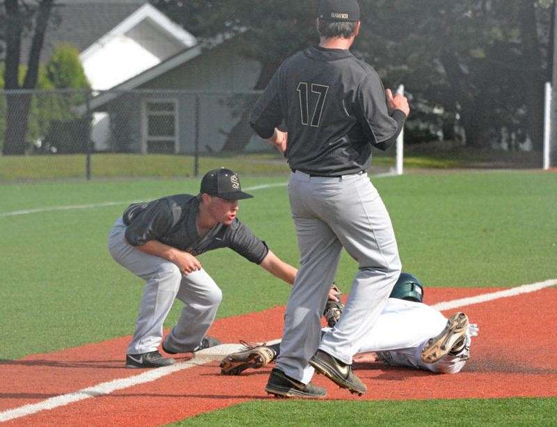 by: TIMES PHOTO: MATT SINGLEDECKER - Southridges Sam Rzepecki puts down a slap tag on Jesuits Ken Carlson for an out on Tuesday.