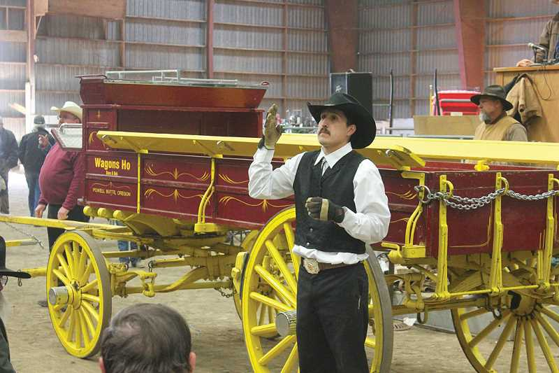by: JEFF WILSON - Auctioneer George Tavera, of Gaston, takes bids on a wagon during Saturday's sale at the annual Small Farmers Journal Auction and Swap at the Jefferson County Fairgrounds.